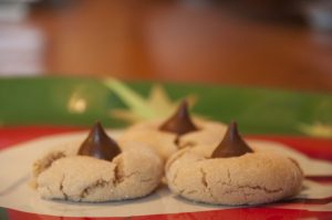Peanut butter and chocolate come together in this perfect, classic Peanut Butter Blossoms recipe. They are so easy to make and a family tradition for every Christmas holiday!