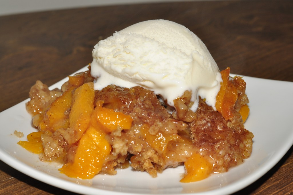 Crock Pot Slow Cooker Peach Cobbler Recipe topped with vanilla icecream