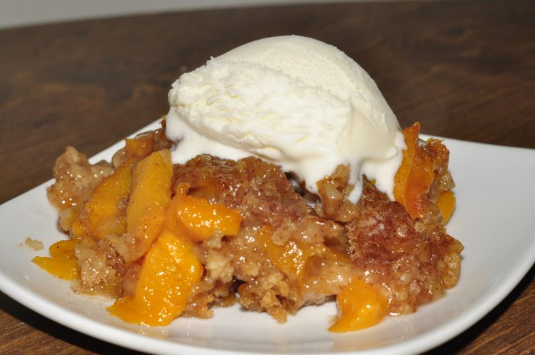 The best and easiest Crock Pot or Slow Cooker Peach Cobbler dessert Recipe topped with warm vanilla icecream