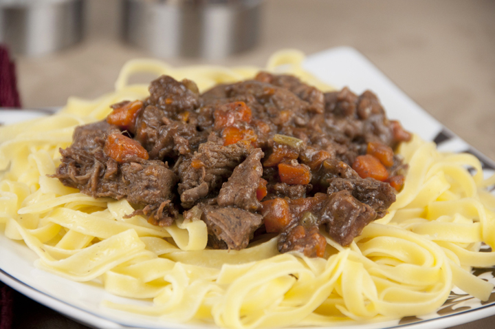 Old Fashioned Beef Stew served over buttered egg noodles