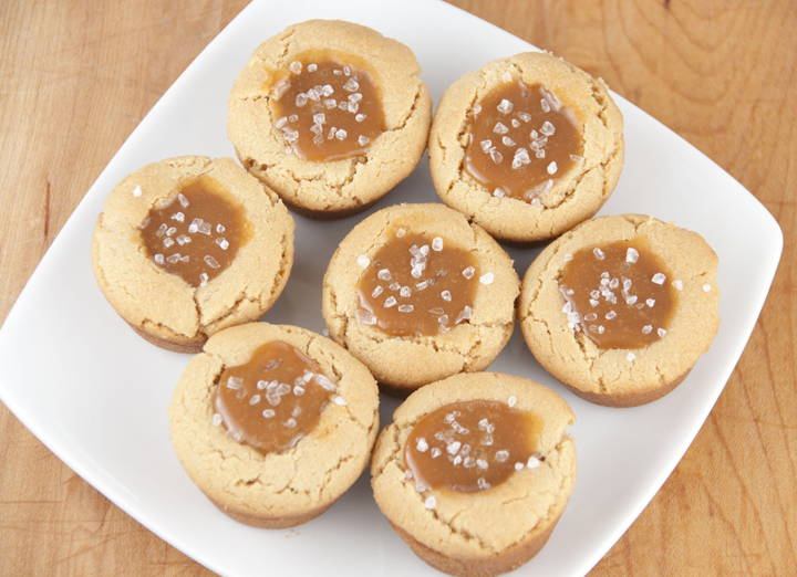 Salted Caramel Peanut Butter Cookie Cups dessert recipe are gooey caramel wrapped in a peanut butter cookie and topped with sea salt for the most peanut buttery of desserts.