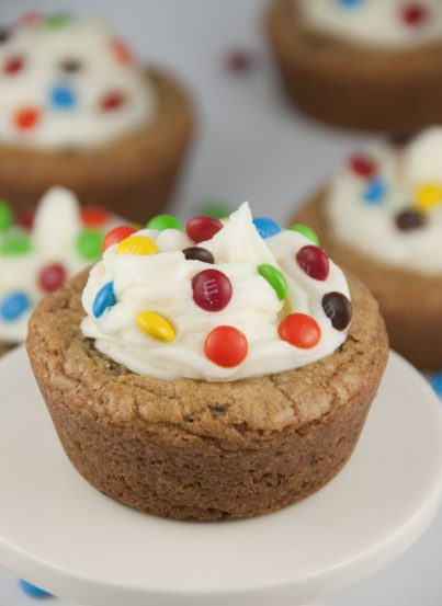 Giant Chocolate Chip Cookie Cups recipe with Almond Buttercream Icing topped with mini M&M's for a fun splash of color make for the perfect dessert for any occasion.
