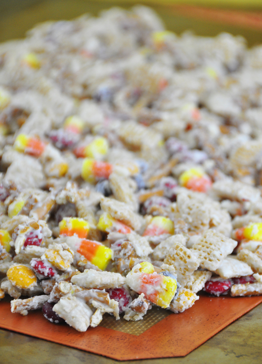 A new twist on party snack mix includes white chocolate, chex cereal, fall M&M's, candy corn, and pretzel sticks for a Halloween treat.