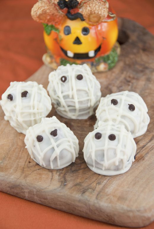 Easy Halloween Mummy Oreo truffles using only three ingredients and mini chocolate chips for eyes!  These are such a simple dessert that kids can help make them.