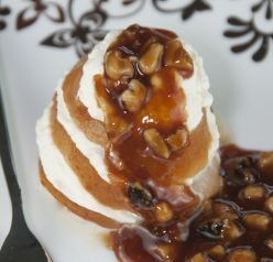 A simple recipe for poached pears in orange juice and topped with cinnamon syrup and walnuts.