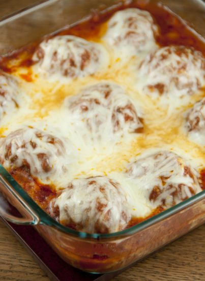 Cheesy meatballs with tomato sauce baked right in the oven - no mess or frying! Good enough for a fancy dinner to serve for a holiday or to dinner guests.