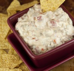 A cheese rotel dip with cooked ground sausage made with minimal ingredients and warmed up right in the crock pot makes a great appetizer for football season, holidays, pot lucks, or tailgating parties!