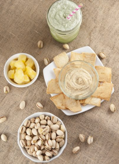 Pistachios, Pineapple bits, hummus and pita chips, and a green tea drink for perfect healthy snacking.