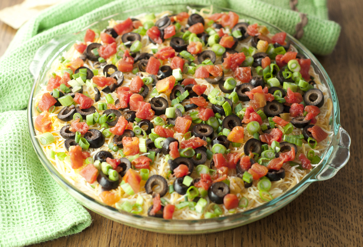 This fiesta 7 layer dip has so many colorful layers of deliciousness. Refried beans, guacamole, sour cream, cheese, spicy tomatoes, olives and green onion make for the perfect party or game day appetizer.