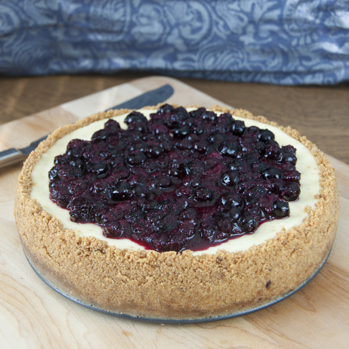 Creamy New York-Style Blueberry Cheesecake recipe with a buttery, thick graham cracker crust and topped with fresh blueberries.  Great for any holiday.