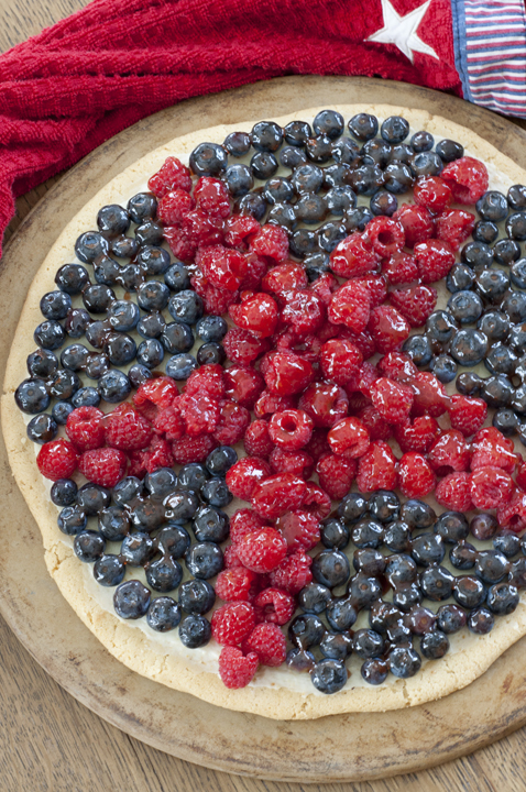 Patriotic Sugar Cookie Fruit Pizza dessert recipe will be the star (no pun intended) of the show at your summer 4th of July party! Fresh, colorful fruit and sweet cream cheese filling give this cookie pizza the perfect combination of pretty and tasty.