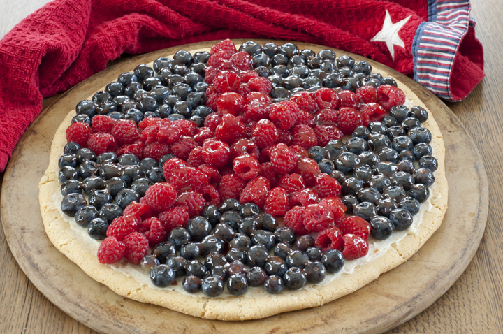 Red, White, and Blue Patriotic Sugar Cookie Fruit Pizza dessert recipe will be the star (no pun intended) of the show at your summer 4th of July party! Fresh, colorful fruit and sweet cream cheese filling give this cookie pizza the perfect combination of pretty and tasty.