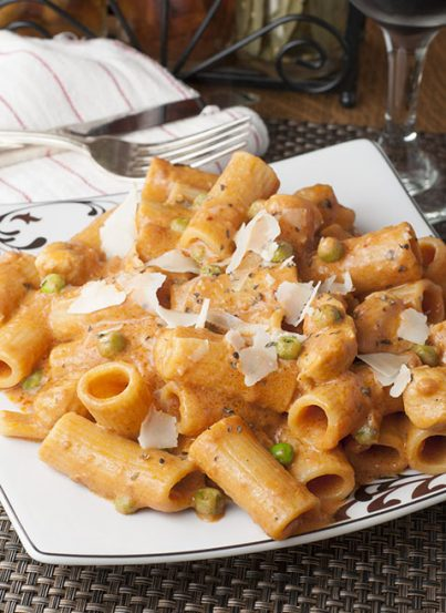 Spicy Chicken Rigatoni recipe is just like my favorite pasta dish at a beloved Italian-American Restaurant. Creamy Alfredo and marinara sauce combine with chicken and peas to make the perfect, easy Italian meal with just the right amount of heat!