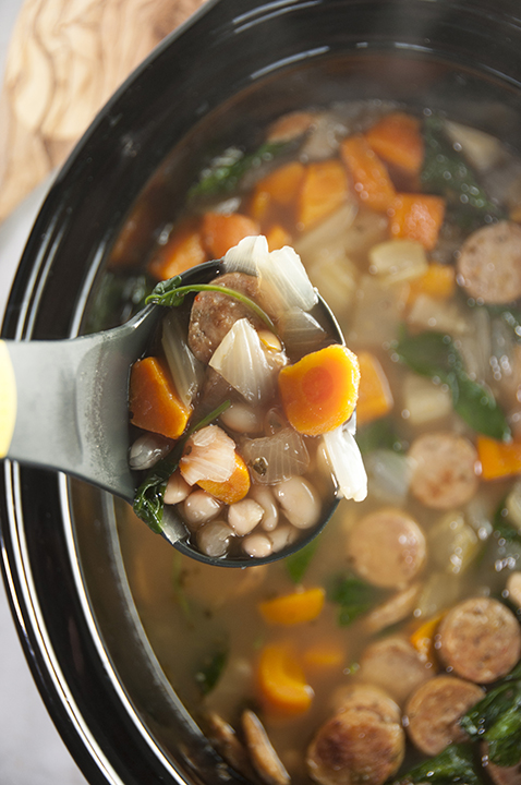 Slow Cooker Sausage, Spinach & White Bean Soup is light, healthy, gluten free, that cooks right in your crock pot. This is made with chicken sausage and is the perfect lunch or dinner for the cooler weather!