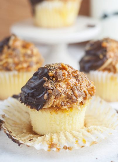 The ultimate soft and fluffy Vanilla Butterfinger Cupcakes are loaded with flavor and the perfect dessert recipe for the candy and peanut butter lover in your life!