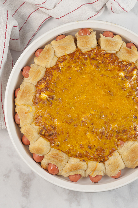 "Chili Cheese Dog Wreath Dip recipe combines a gooey cheesy, chili dip surrounded by cocktail wiener ""pigs in a blanket"" for a popular appetizer dip at your next party, holiday or Super Bowl gathering!"