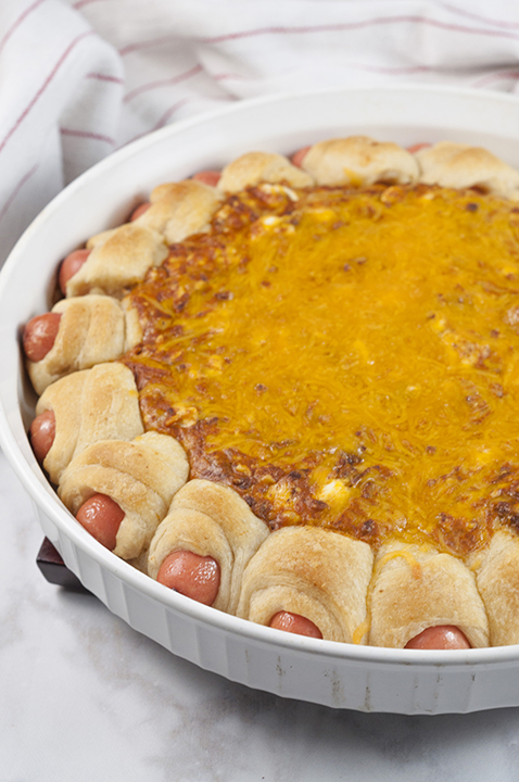 Chili Cheese Dog Wreath Dip recipe combines a cheesy, chili dip surrounded by perfectly baked pigs in a blanket for a show-stopping dip at your next party or Super Bowl!