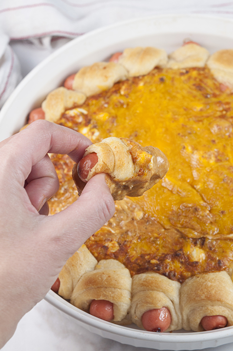 Chili Cheese Dog Wreath Dip recipe combines a cheesy, chili dip surrounded by perfectly baked pigs in a blanket for a winning dip at your next party, holiday or for the big game!