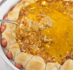 "Chili Cheese Dog Wreath Dip appetizer recipe combines a gooey, cheesy, chili dip with cocktail wiener ""pigs in a blanket"" for the best dip at your next party, holiday or Super Bowl!"