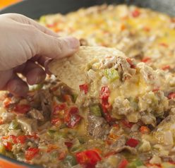 Philly Cheesesteak Dip recipe is made up of tender beef, colorful peppers, and loads of ooey gooey cheese. Perfect for game day, holidays or an appetizer to serve at a party!