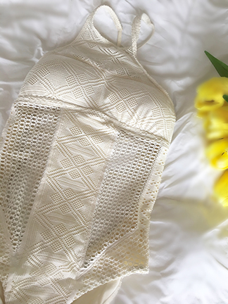 Vitamin A Swimwear review: one piece off-white bathing suit with crocheted detail perfect for any beach vacation.