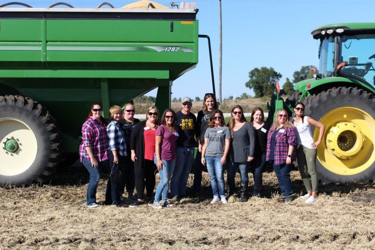 Group photo at Kenney farm in front of the Combine.