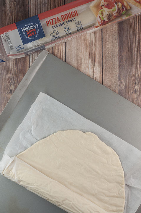 Unrolling the Pillsbury pizza dough to bake in the oven.