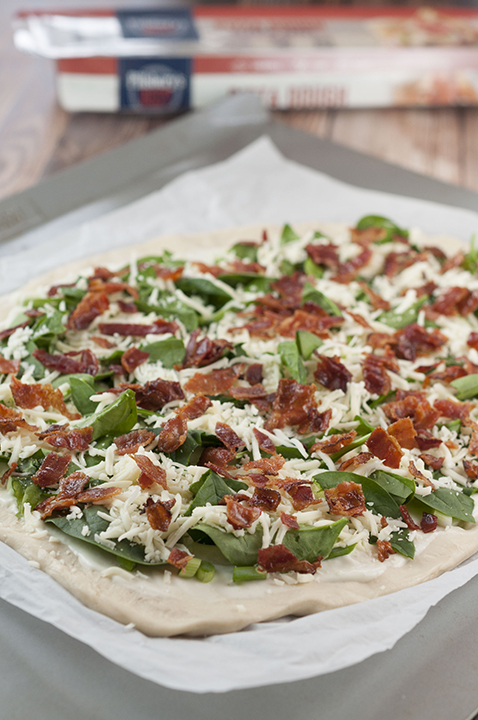 Spreading the bacon and spinach onto the Bacon Alfredo Pizza prior to baking.