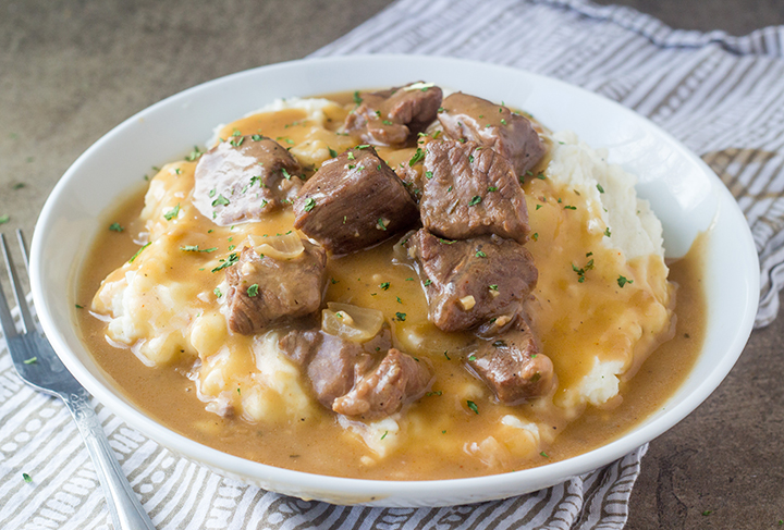 Crock Pot or Slow Cooker Beef Tips and Gravy is perfect to serve to dinner guests but simple enough for a weeknight supper recipe! Serve it over noodles, potatoes or rice!