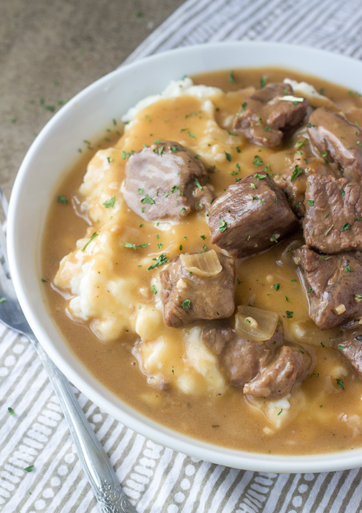 Slow Cooker Beef Tips and Gravy is perfect to serve to dinner guests but simple enough for a weeknight dinner recipe (such as New Year's Eve supper)! Serve it over noodles, potatoes or rice!