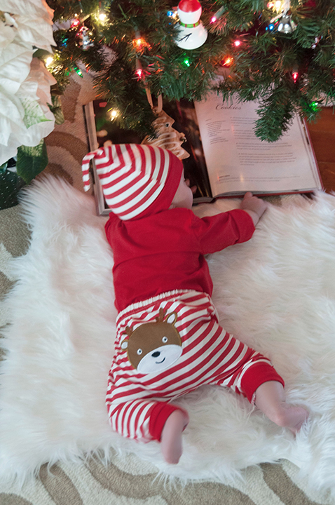 Baby Eliza reading a book under the Christmas tree.