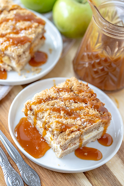 Salted Caramel Apple Cheesecake Bars is a great fall baking recipe with a shortbread crust, cheesecake filling, and an irresistible streusel topping. The salted caramel drizzle makes these the perfect fall dessert for Thanksgiving or Christmas!