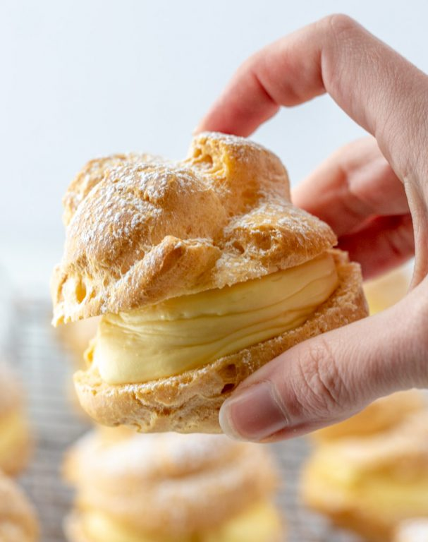 My famous authentic Homemade Cream Puffs recipe: light and airy cream puffs filled with vanilla pudding cream are always a hit with family and anyone I've served them to. If you want an impressive, pretty dessert for Christmas, Easter, or any holiday, this one is it!