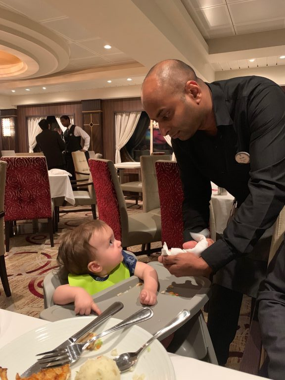 Fun waitstaff with the baby at the main dining room on board Royal Caribbean Symphony of the Seas cruise.