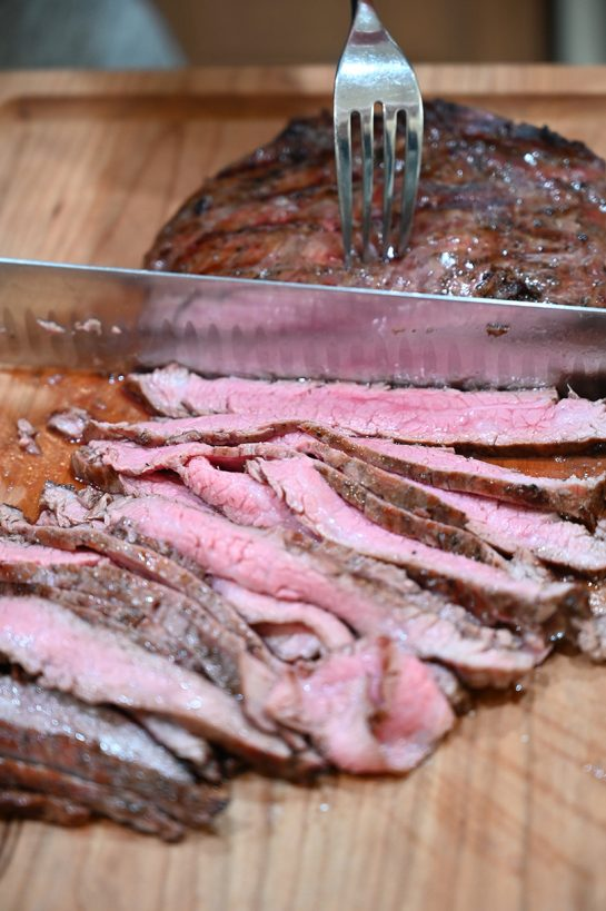 Slicing grilled flank steak against the grain.