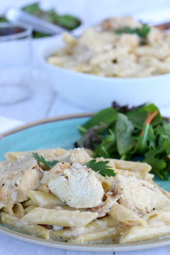Chicken Alfredo plated with a side salad for an easy crock pot pasta dinner recipe.