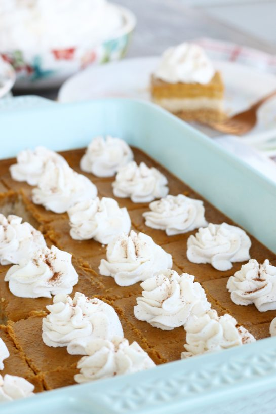 Pumpkin cheese cake bars cut into individual sized servings and topped with fresh whipped cream.