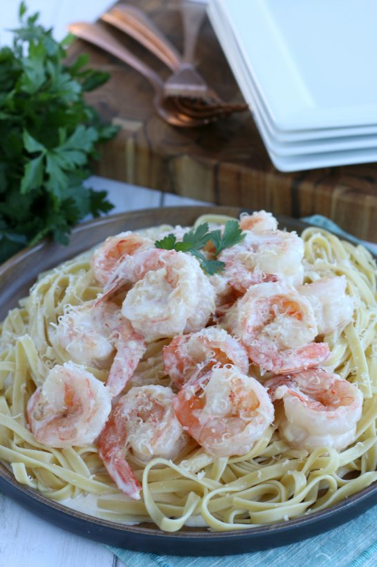 Beautifully plated shrimp with garlic sauce layered over pasta for an easy dinner recipe.