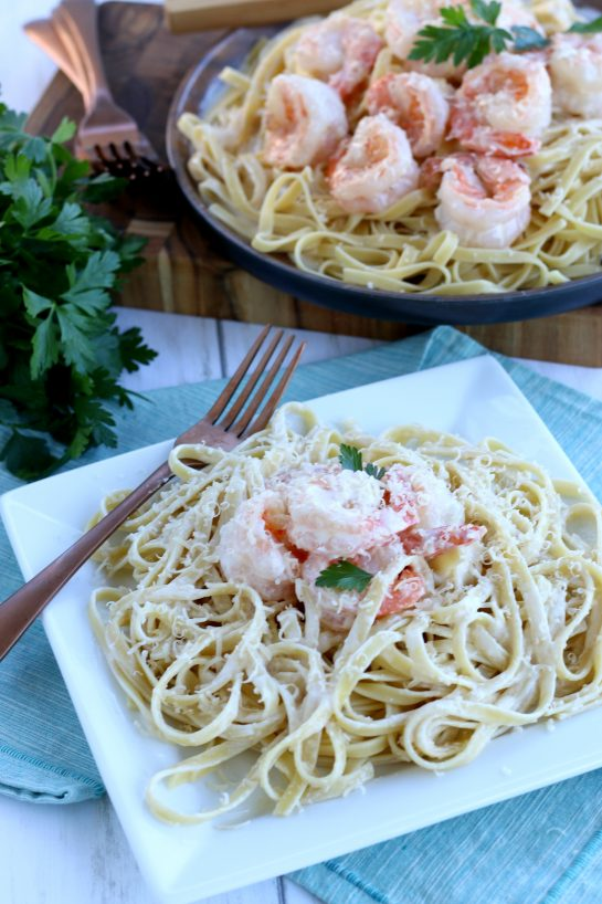 Shrimp with garlic sauce on a plate ready to eat with some more garlic butter sauce and cheese sprinkled over the top.