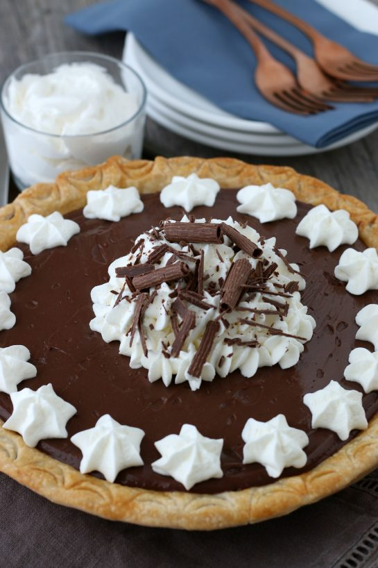Homemade chocolate pie or old fashioned chocolate pie is easy to make and uses homemade chocolate pudding! How to make chocolate pie! Finished homemade chocolate pudding pie topped with whipped cream and ready to be served.