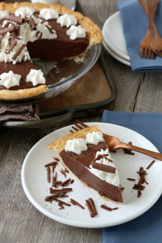 Finished homemade chocolate pie sliced and served on a plate, ready to be enjoyed.