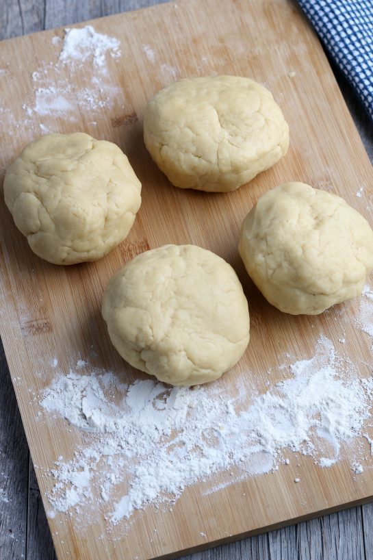The dough is separated into four balls to make Italian fig cookies.