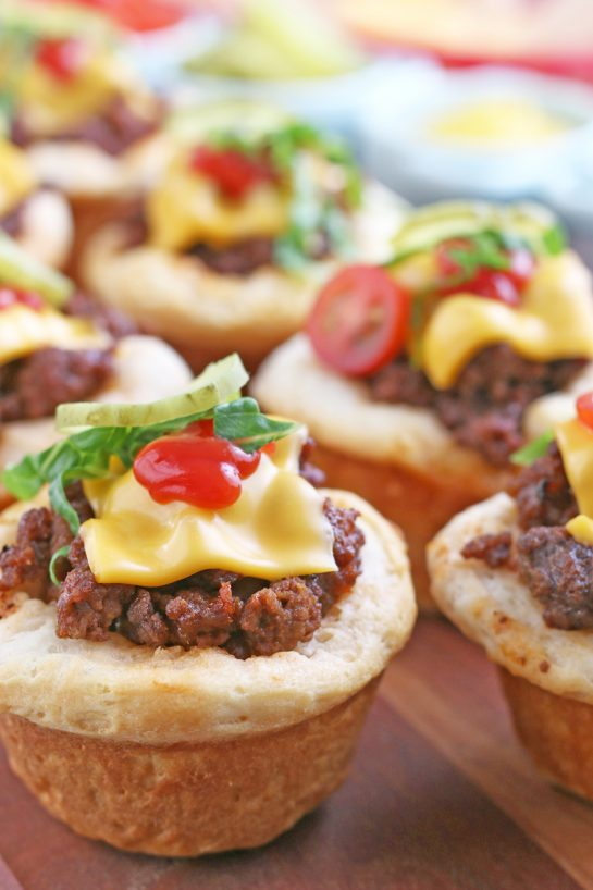 Here we see the finished cheeseburger biscuit bites finished and topped with veggies to eat! Great for Super Bowl appetizer!