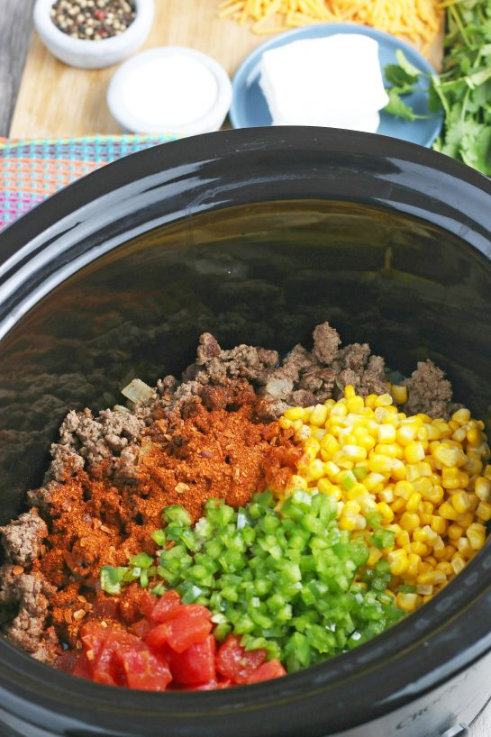 More seasonings and vegetables go into our Mexican pasta salad as we layer up the slow cooker!