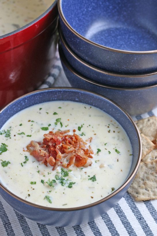 A bowl of soup with crispy bacon added on top ready to be enjoyed.