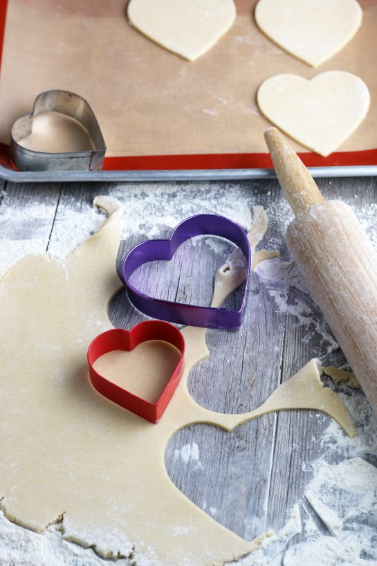 Here we see the batter rolled out and being cut with heart shaped cookie cutters before they're baked!