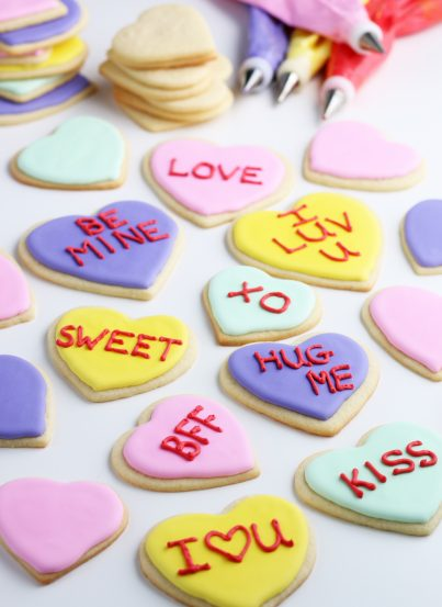 This image shows the Valentines cookies in various states of decoration, some are finished, others need writing and frosting!