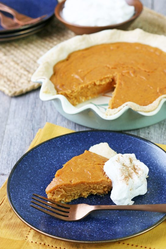A slice of the sweet potato pie on a plate with whipped cream ready to be enjoyed.