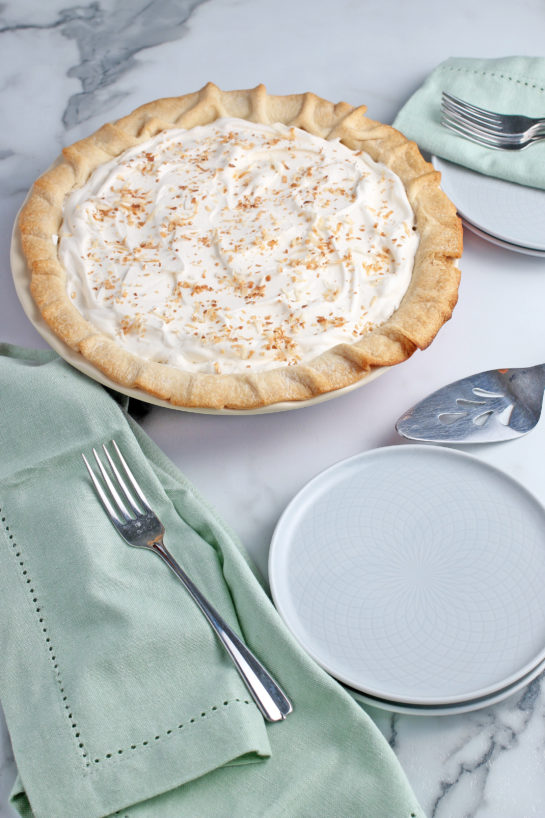 The best coconut cream pie, finished, shown with plates and silverware for serving!