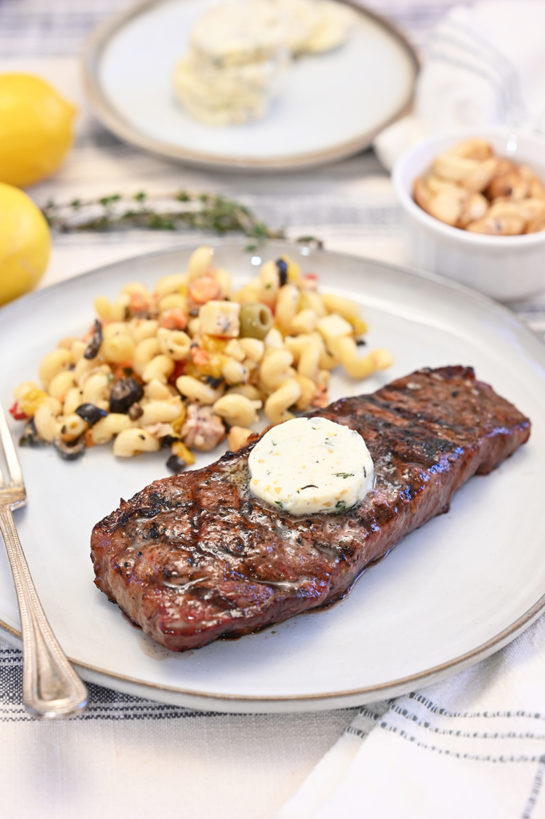 Summer Grilled Strip Steaks with Herb Compound Butter is a gourmet dinner at home! The compound butter is an easy and flavorful topping to add extra flavor to your steak!